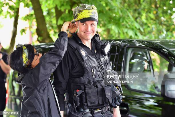 An armed police officer tries on a bee pattern headscarf as music fans arrive at the Old Trafford Cricket Ground ahead of the One Love Manchester...