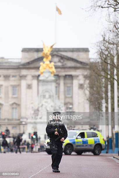 An armed police officer walks along the Mall in front of Buckingham Palace ahead of the Changing of the Guard ceremony on December 21 2016 in London...