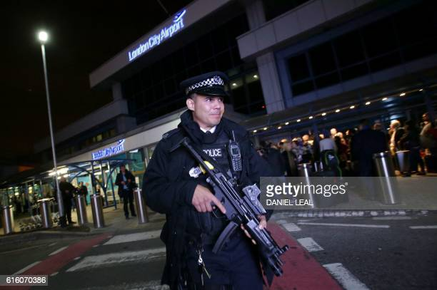 An armed police officer walks outside the entrance to London's City Airport as passengers queue on October 21 2016 after an evacuation Hundreds of...