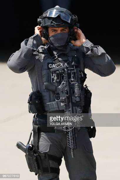 An armed police officier waits on the tarmac at Stansted Airport north of London on July 12 ahead of the arrival of US President Donald Trump on Air...