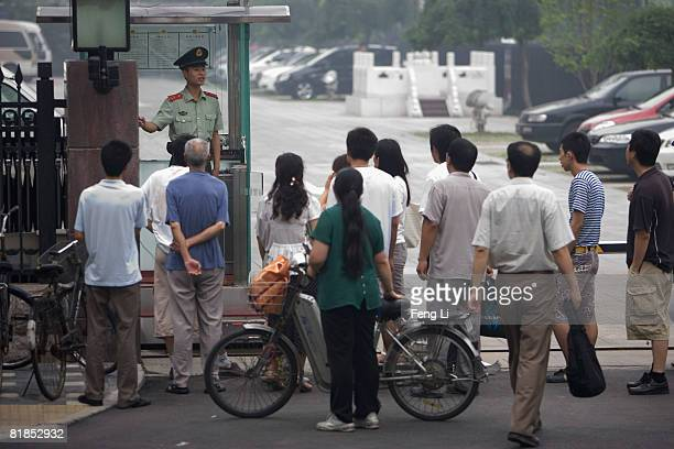 An armed policeman advises residents to leave after they have gathered at the gate of the People's Bank of China to exchange their money for the new...