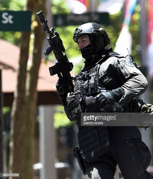 An armed policeman is seen outside a cafe in the central business district of Sydney on December 15 2014 Hostages were being held inside a cafe in...