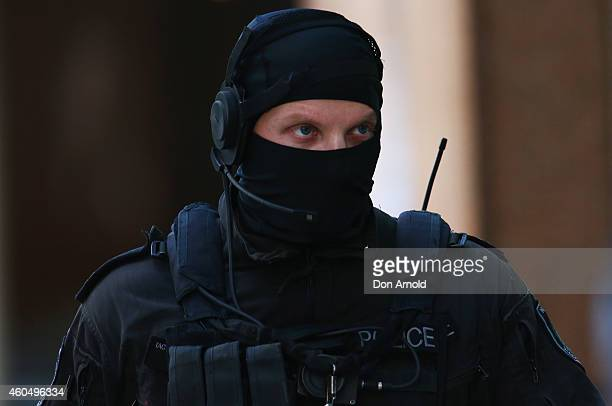 An armed policeman looks on from Philip St near the Lindt Cafe Martin Place on December 15 2014 in Sydney Australia Police attend a hostage situation...