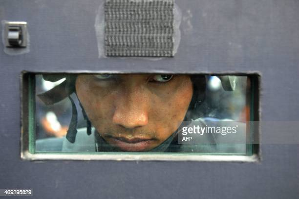 An armed policeman observes the demonstration by anti-government protestors near the Government House building in Bangkok on February 14, 2014....
