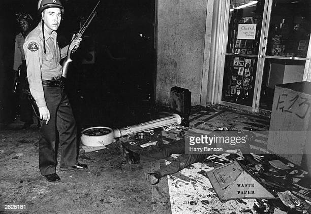An armed policeman stands beside the body of a black American protester during the race riots in the Watts district of Los Angeles 11th15th August...