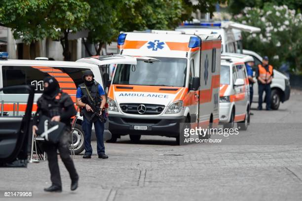 An armed policeman stands next to ambulance cars in the old quarter of Schaffhausen northern Switzerland on July 24 after a man armed with a chainsaw...