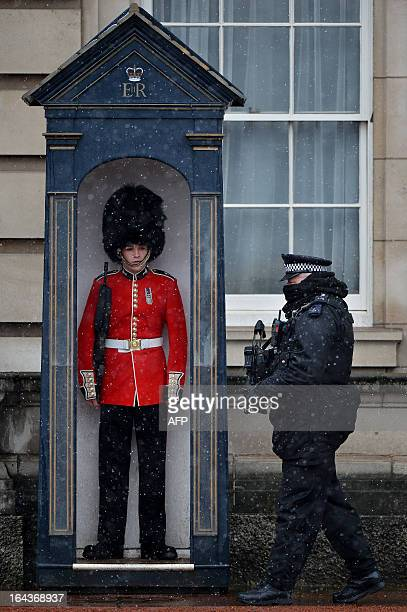 An armed policeman walks past a member of the 1st Battalion Welsh Guards standing in a guards box as snow falls at Buckingham Palace in central...