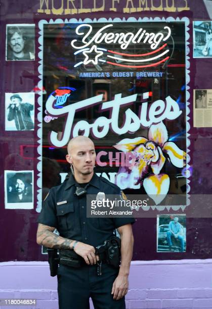 An armed private duty guard stands near the entrance to Tootsie's Orchid Lounge an iconic bar and live country music venue in the Lower Broadway...