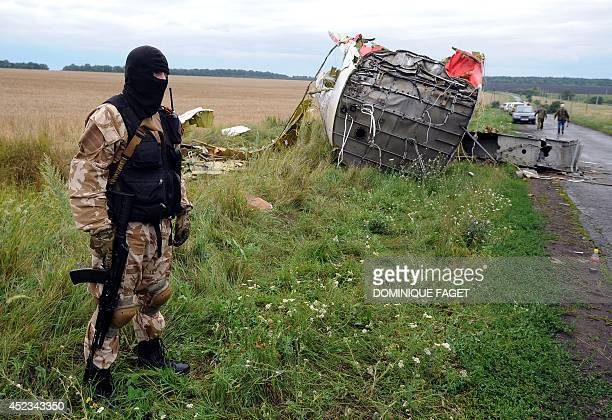 An armed proRussia militant stands guard at the site of the crash of a Malaysian airliner carrying 298 people from Amsterdam to Kuala Lumpur in...