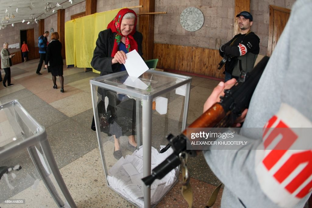 An armed pro-Russian activists stands guard as a woman casts her ballot for the referendum called by pro-Russian rebels to split from the rest of Ukraine, , on May 11, 2014 in Donetsk. The vote, carried out as two 'referendums' in provinces where the insurgents hold more than a dozen towns, marks a serious deepening of the political crisis in Ukraine, which has pushed East-West relations to lows not seen since the end of the Cold War.