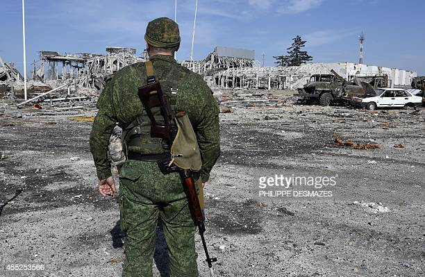 An armed proRussian militants walks in front the destroyed Lugansk International Airport eastern Ukraine on September 11 2014 ProRussian separatists...