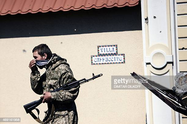 An armed proRussian rebel walks down street in the village of Spartak near the airport of Donetsk on April 10 2015 Amnesty International said it had...