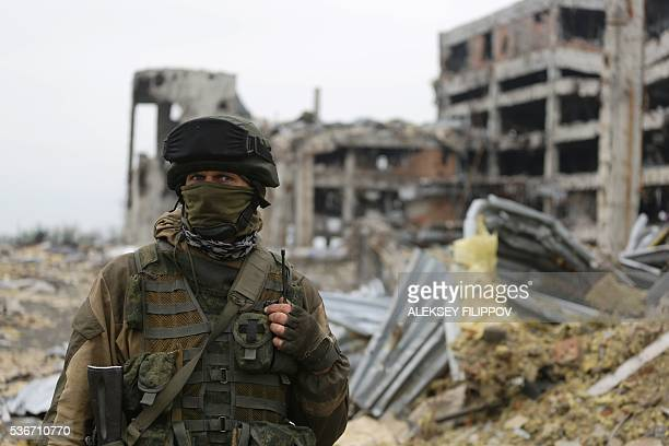 An armed proRussian separatist of the selfproclaimed Donetsk People's Republic stands in front of the destroyed Donetsk International Airport in...