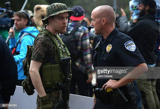 An armed protester from the socalled Bureau of AmericanIslamic Relations speaks with a policeman at a demonstration in front of the Islamic...