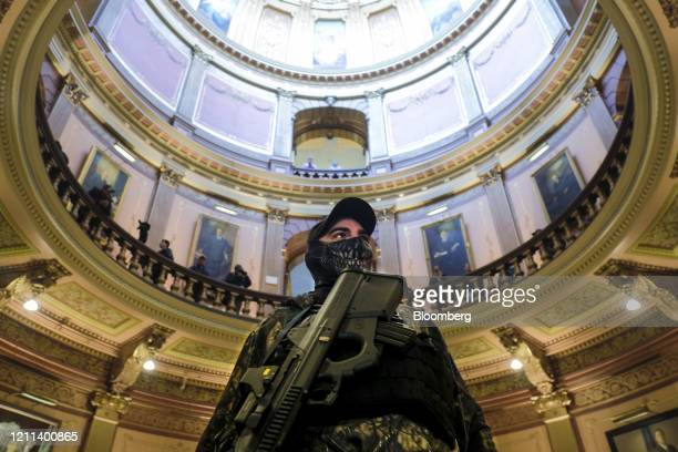 An armed protester wearing a mask stands at the Michigan Capitol Building in Lansing, Michigan, U.S., on Thursday, April 30, 2020. Protesters...