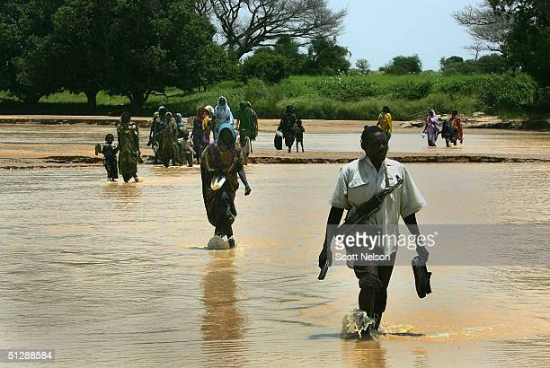 An armed rebel fighter from the Sudanese Justice and Equality Movement escorts a group of Sudanese refugees across a river into neighbouring Chad...