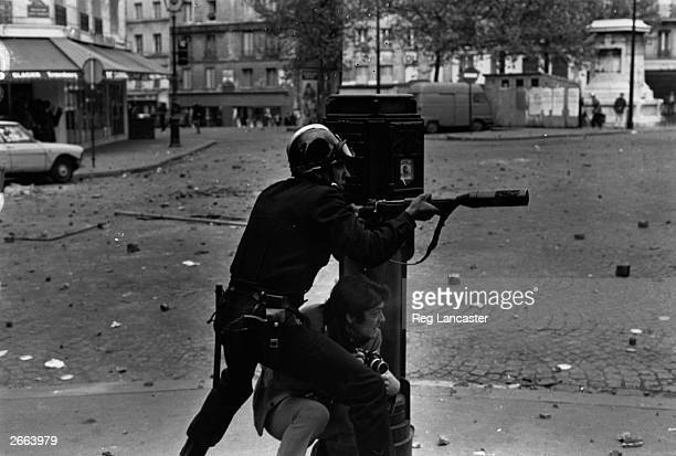 An armed riot policeman and a photographer take cover during student riots in the streets of Paris