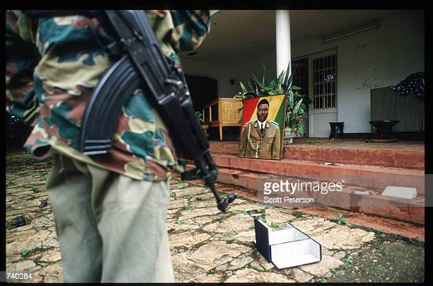 An armed Rwandan Patriotic Front soldier stands in front of the home of Major General JuvTnal Habyarimana May 26 1994 in Kigali Rwanda Habyarimana...