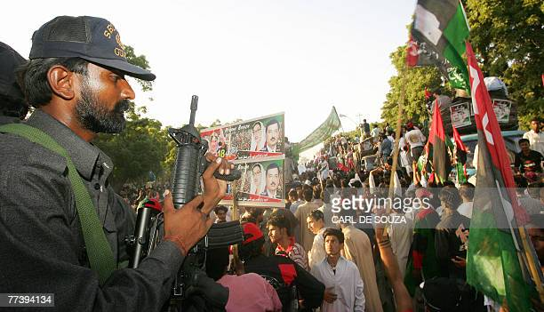 An armed security guard keeps watch over supporters of former Pakistani Prime Minister Benazir Bhutto outside Karachi international airport 18...