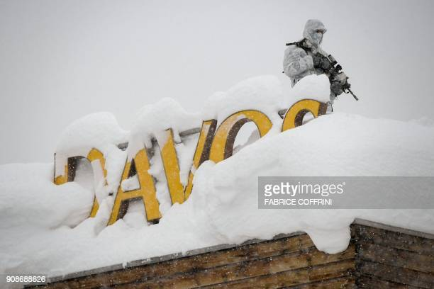 TOPSHOT An armed security personnel wearing camouflage clothing stands on the rooftop of a hotel next to letters covered in snow reading 'Davos' near...