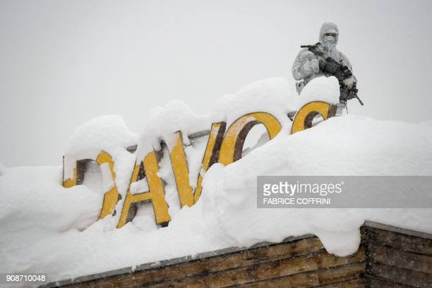 An armed security personnel wearing camouflage clothing stands on the rooftop of a hotel next to letters covered in snow reading 'Davos' near the...