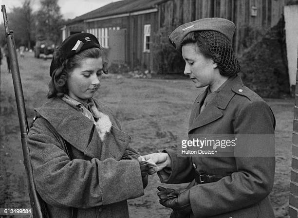 An armed sentry checks the pass of Aline Karpowics as she leaves camp after being among prisoners released by the British, 1945.