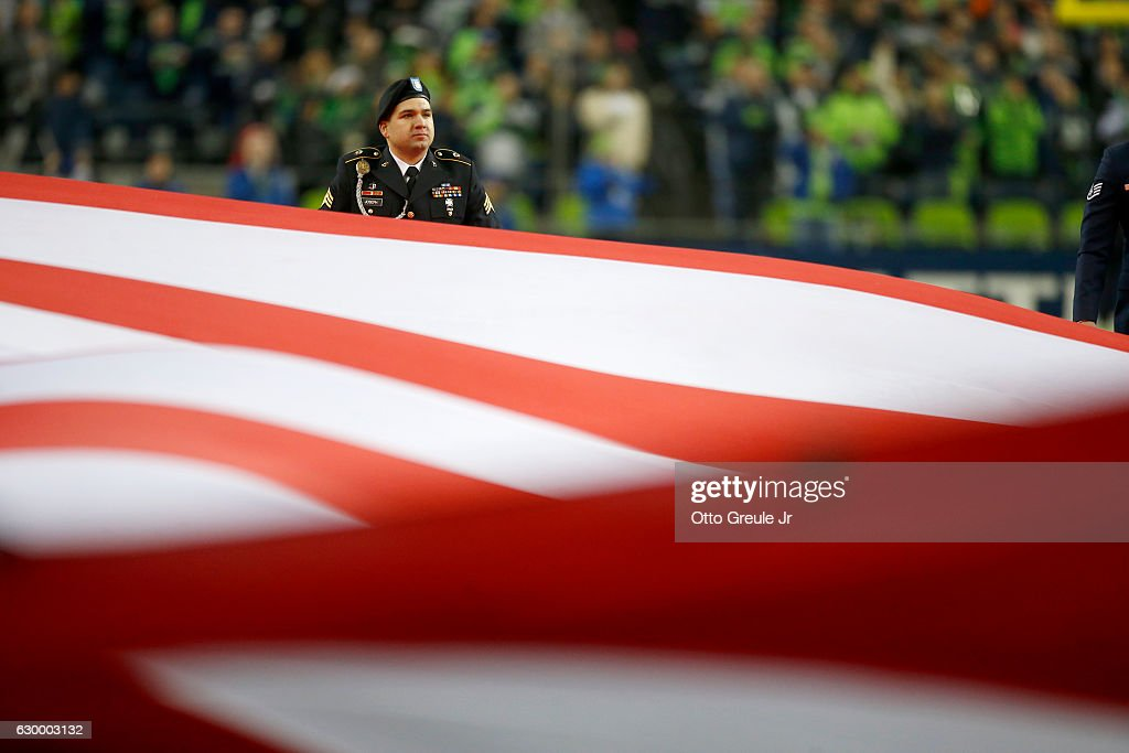 An armed services member participates in opening ceremonies for an NFL game between the Seattle Seahawks and the Los Angeles Rams at CenturyLink Field on December 15, 2016 in Seattle, Washington.
