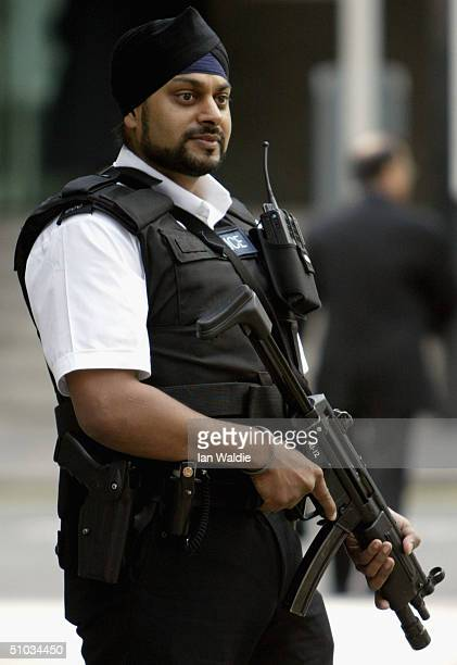 An armed Sikh Metropolitan Police officer patrols the streets of Westminster July 8 2004 in London