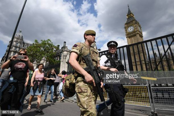 An armed soldier and an armed police officer patrol outside the Houses of Parliament on May 24, 2017 in London, England. 984 military personnel are...