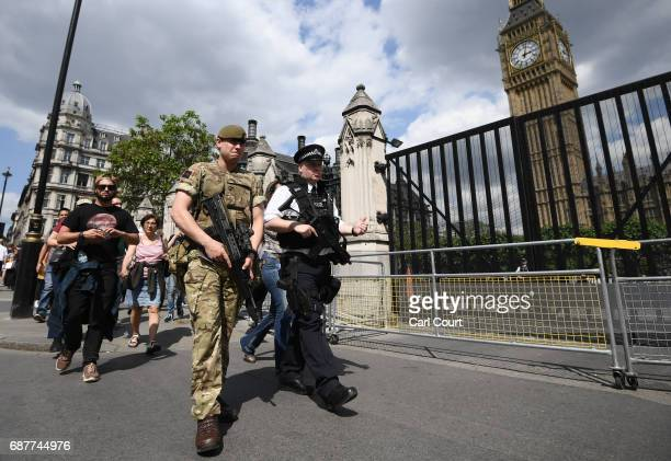 An armed soldier and an armed police officer patrol outside the Houses of Parliament on May 24 2017 in London England 984 military personnel are...