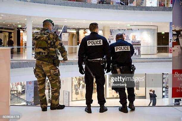 An armed soldier and police officers stand guard on a balcony during the first day of new year retail sales in the Beaugrenelle shopping mall in...