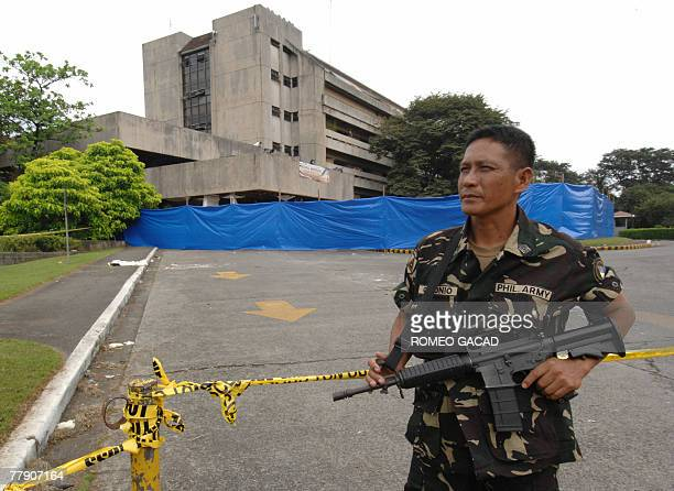 An armed soldier guards the sealed damaged southern section of the House of Representatives in Manila 14 November 2007 following a bomb attack that...