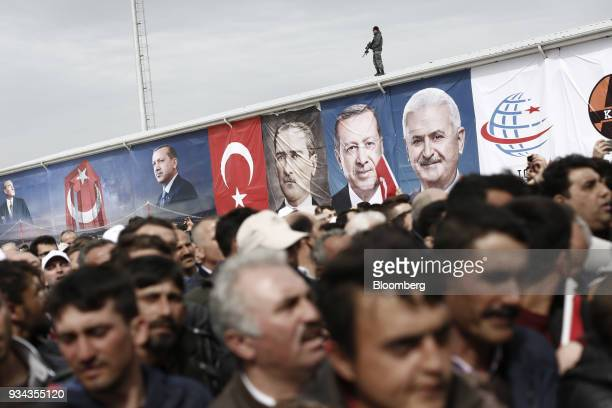 An armed soldier watches as supporters of Turkey's President Recep Tayyip Erdogan attend a ceremony for the first concrete casting of the 1915...