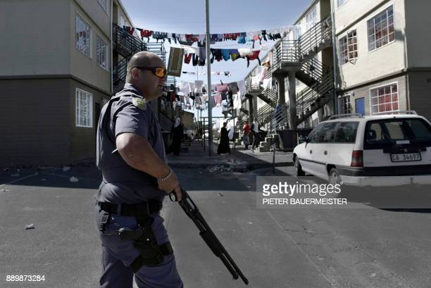 An armed South African police officer patrols in a street as he responds to a shooting of two alleged gang members in Manenberg Cape Town on October...