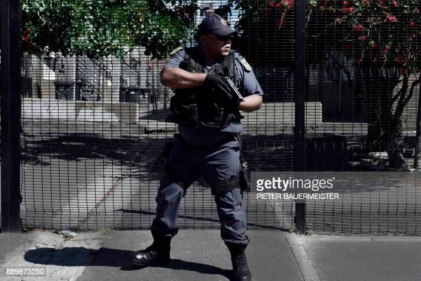 An armed South African police officer responds to a shooting of two alleged gang members in Manenberg on October 18 2017 in Cape Town A rise in...