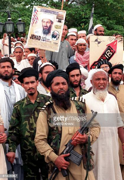 An armed supporter of Pakistan's religiouspolitical party Jamait UlmaiIslam stands in front of the portrait of Saudi dissident Osama bin Laden during...