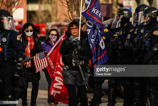 An armed supporter of President Donald Trump walks through a line of law enforcement personnel during a rally on December 12, 2020 in Olympia,...