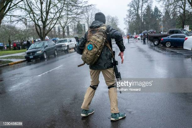 An armed supporter of President Trump reaches for his rifle while walking past the state capital on January 6, 2021 in Salem, Oregon. Trump...