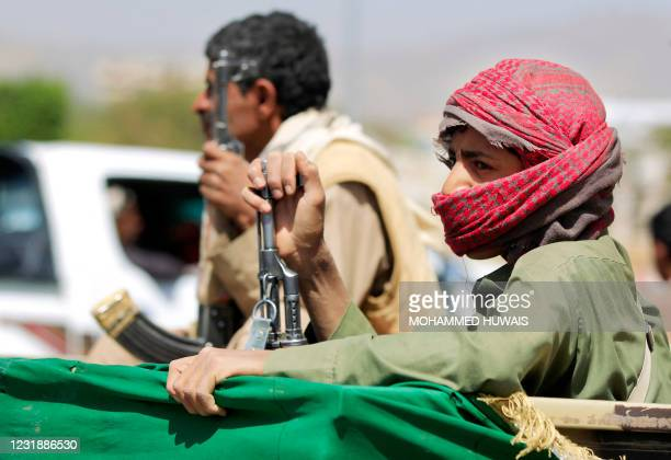 An armed supporter of Yemen's Huthi rebels sits in the back of a pick up during the funeral procession for fighters killed in battles with...