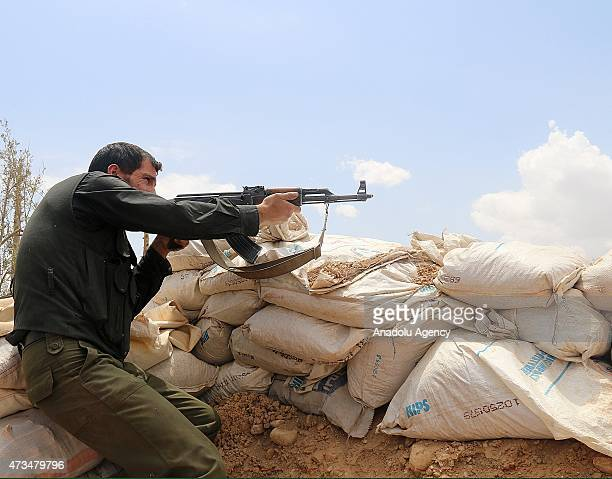 An armed Syrian opponent carries a kalashnikov at a ditch in the Haresta neighborhood of Damascus Syria on May 15 2015 before they attack regime...