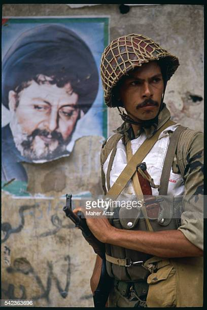 An armed Syrian soldier is standing on a Beirut street with a torn poster of Shia cleric Mousa Sadr behind him | Location South Beirut Lebanon
