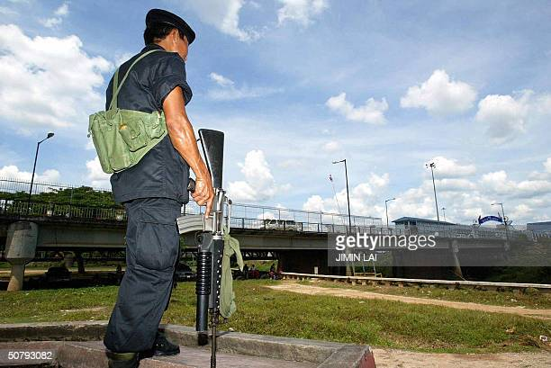 An armed Thai army ranger stands guard near the bridge which crosses the Kolok River into Malaysia at the border town of Kolok 02 May 2004 Violence...