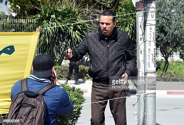 An armed Tunisian policeman in plainclothes stops a photographer as security forces secure the area after gunmen attacked Tunis' famed Bardo Museum...
