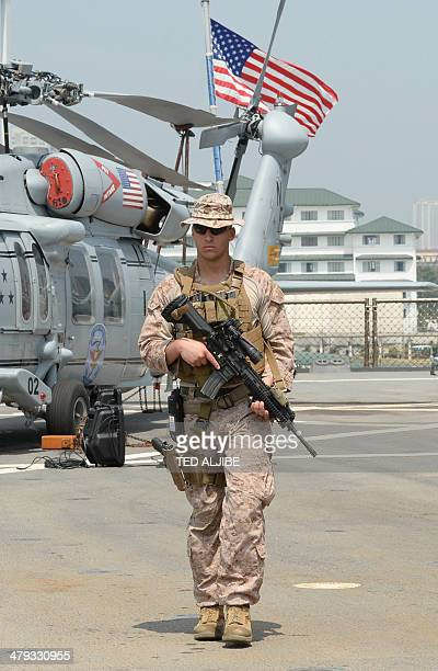 An armed US marine patrols next to seahawk helicopters on the deck of 7th Fleet command ship, USS Blue Ridge shortly after arriving at the...