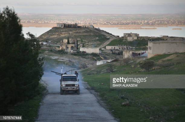 An armed vehicle driven by Turkeybacked Syrian fighters is seen in a village overlooking the Euphrates river near the rebelheld border town of...