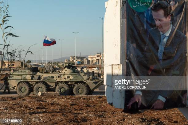 An armed vehicle is parked near a portrait of Syrian President Bashar alAssad as Russian soldiers distribute humanitarian aid in Rastan central Homs...