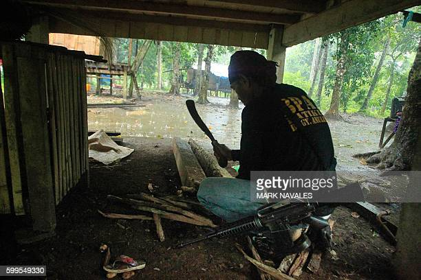 An armed villager who volunteered to fight against the Abu Sayyaf group cuts firewood as he keeps his M16 assault rifle by his side in Patikul town...