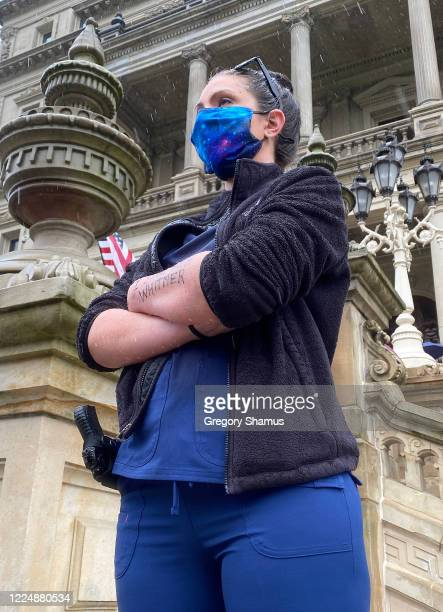 An armed woman stands in support of Governor Gretchen Whitmer while protesters gather at the Michigan Capitol Building on May 14 2020 in Lansing...