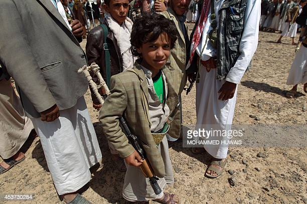 An Armed Yemeni boy loyal to the Shiite Huthi movement attends a tribal gathering against alQaeda militants in the Bani alHarith area north of Sanaa...