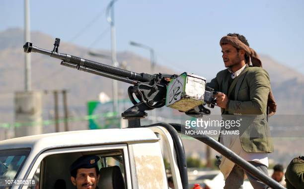 An armed Yemeni man holds his weapon as people gather in the capital Sanaa to show their support to the Shiite Huthi movement against the Saudiled...